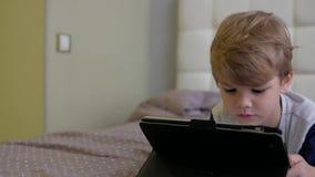 Tableta de observación del muchacho mientras que miente en cama