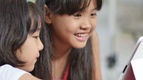 Tableta de observación del pequeño niño asiático en parque almacen de metraje de vídeo