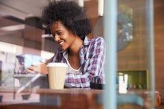 Tableta de On Phone Using Digital de la empresaria en cafetería Imagen de archivo