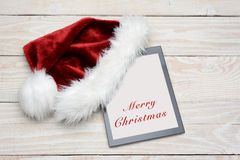 Tableta de Santa Hat With Happy Holidays Imagenes de archivo