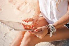 Tableta de tacto de la mujer en la playa imagenes de archivo