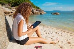 Tableta de tacto de la mujer en la playa fotos de archivo libres de regalías