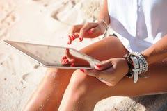 Tableta de tacto de la mujer en la playa fotos de archivo