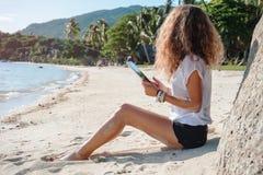 Tableta de tacto de la mujer en la playa imagen de archivo libre de regalías