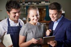 Tableta de Team Discussing Menu Looking At Digital del restaurante imagen de archivo libre de regalías