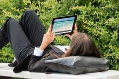 Tableta de Watching Video On Digital de la empresaria fotos de archivo libres de regalías