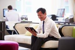 Tableta de Working On Digital del hombre de negocios en pasillo del hotel Fotos de archivo libres de regalías