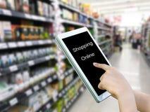 Tableta del control de la mano que hace compras en línea, fondo borroso de la tienda Imagen de archivo