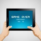 Tableta del control de la mano que juega al juego Fotos de archivo