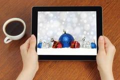 Tableta del control de las manos con la composición de la Navidad Foto de archivo