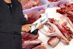 Tableta del control del hombre de negocios y cerdo fresco en el mercado, negocio comercial del cerdo foto de archivo