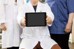 Tableta del doctor Showing Blank Digital mientras que se sienta por el equipo foto de archivo