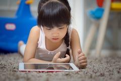 Tableta del juego de niños en la alfombra de la sala de estar Fotografía de archivo libre de regalías