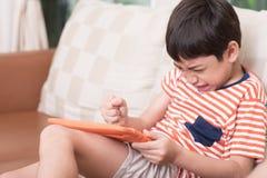 Tableta del juego del juego del niño pequeño con la sensación enojada Fotografía de archivo