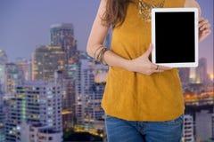 Tableta del ordenador del control de la mujer de negocios con con el edificio en backgr Imagen de archivo libre de regalías