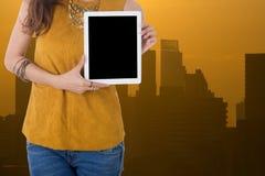 Tableta del ordenador del control de la mujer de negocios con con el edificio en backgr Foto de archivo