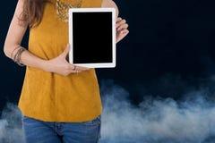 Tableta del ordenador del control de la mujer de negocios con humo en fondo Fotos de archivo libres de regalías