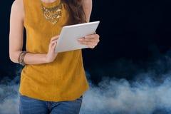 Tableta del ordenador del control de la mujer de negocios con humo en fondo Fotografía de archivo libre de regalías