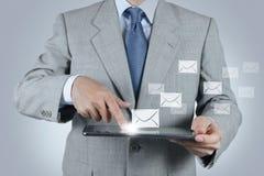 Tableta del uso de la mano con el icono del correo electrónico Imágenes de archivo libres de regalías