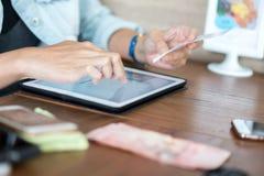 Tableta del uso de la mano para hacer compras en línea fotos de archivo