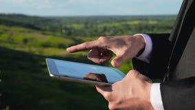 Tableta digital conmovedora de la mano del hombre de negocios almacen de video