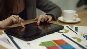 Tableta digital conmovedora de las manos femeninas en el escritorio de oficina almacen de video