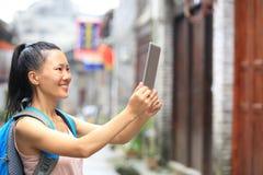 Tableta digital de la mujer del espacio en blanco asiático joven del control Fotos de archivo