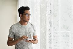 Tableta digital de la tenencia adolescente asiática mientras que mira fuera de su apartamento Fotografía de archivo