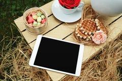 Tableta digital de la visión superior que miente en la caja de madera con imágenes de archivo libres de regalías