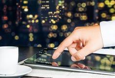 Tableta digital del tacto del hombre de negocios en el periódico de negocios Imagen de archivo