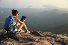 Tableta digital del uso del caminante de la mujer en el pico de montaña fotografía de archivo