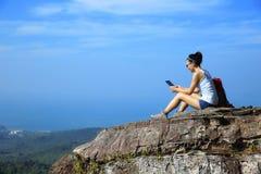 Tableta digital del uso del caminante de la mujer en la montaña Foto de archivo libre de regalías
