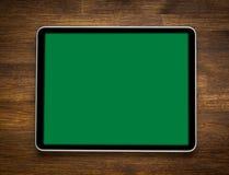 Tableta digital moderna en blanco en un escritorio de madera tapa Imagen de archivo libre de regalías