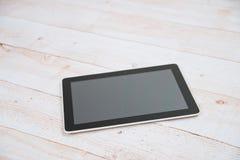 Tableta digital negra en la tabla de madera Fotos de archivo libres de regalías