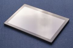 Tableta digital negra en las hojas azules del paño imagen de archivo libre de regalías