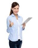 Tableta digital y pulgar del uso asiático de la mujer para arriba Fotografía de archivo