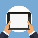 Tableta a disposición en un fondo azul Fotos de archivo libres de regalías