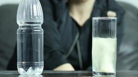 Tableta efervescente del primer en el vidrio de agua, mujer joven suicida deprimida subrayada 4K almacen de metraje de vídeo