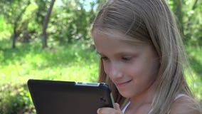 Tableta el jugar de niño al aire libre en la naturaleza, muchacha sonriente en los juegos 4K de la PC de los juegos del oscilació almacen de video