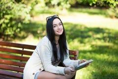 Tableta electrónica de la estudiante que se sienta en un banco fotografía de archivo libre de regalías