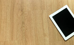 Tableta en el piso de madera Imágenes de archivo libres de regalías