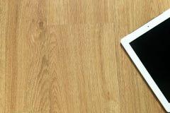 Tableta en el piso de madera Fotos de archivo