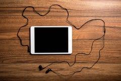 Tableta en la madera con los auriculares Fotografía de archivo libre de regalías