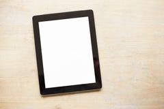 Tableta en la tabla de madera Imágenes de archivo libres de regalías