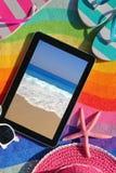 Tableta en la toalla de playa Foto de archivo libre de regalías
