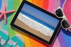 Tableta en la toalla de playa Foto de archivo