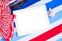 Tableta en las toallas de playa con tomar el sol los accesorios Imagen de archivo libre de regalías