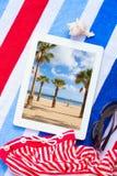 Tableta en las toallas de playa con tomar el sol los accesorios Foto de archivo