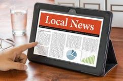 Tableta en un escritorio - noticias locales Imagen de archivo libre de regalías