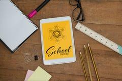 Tableta en una tabla de la escuela con los iconos de la escuela en la pantalla Imagen de archivo